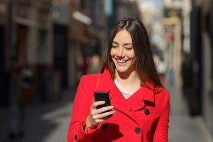 Woman using a smart phone while walk in the street