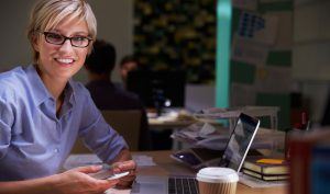 Female Office Worker With Coffee At Desk Working Late