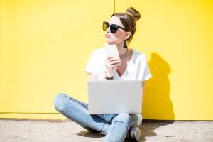 Young woman working with laptop sitting on the yellow wall background outdoors